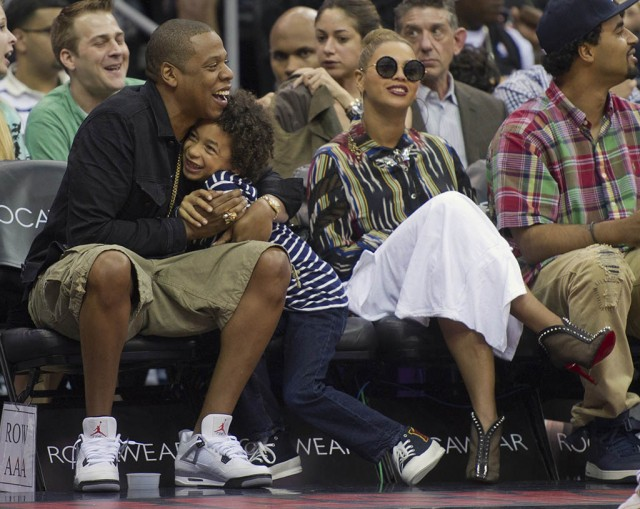 Rapper Jay-Z hugs nephew Smith as his wife, singer Beyonce watches the New Jersey Nets play the Miami Heat in the third quarter of their NBA basketball game in Newark, New Jersey